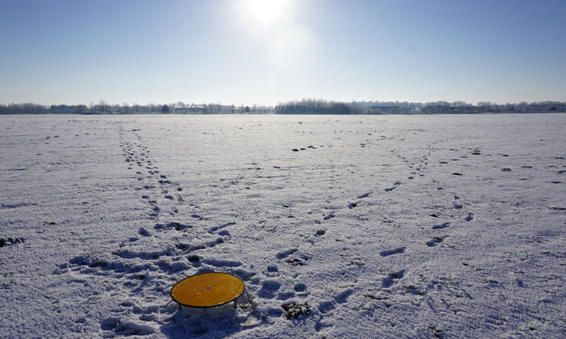 Routescene yellow survey target on site in snow under the sun.