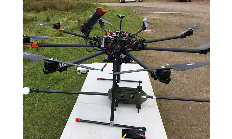 Close up of multicopter UAV with Routescene mounting kit and dual antenna on a table outdoors ready for set up.
