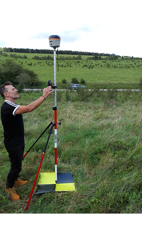 Male engineer setting up Routescene ground station GPS equipment on tripod in the field.