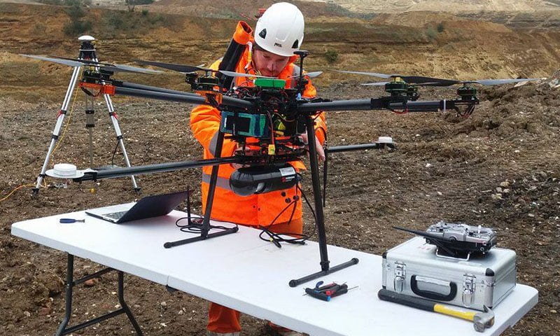 Male professional UAV pilot in orange hi-vis clothing setting up Routescene LidarPod underneath UAV in field.