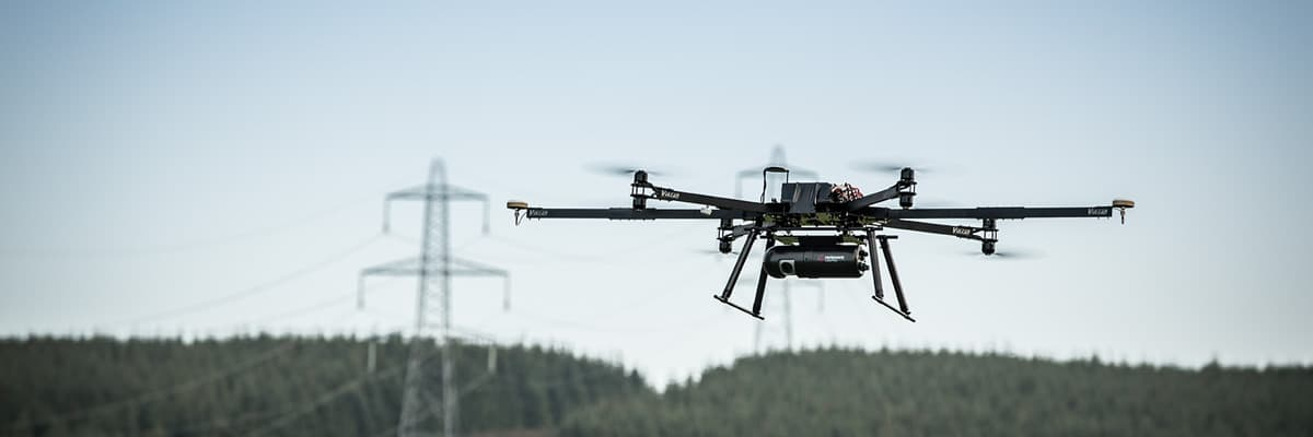 LidarPod on UAV in flight over forest with powerline in background