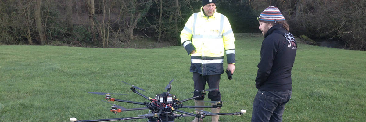 Two professional UAV pilots discussing drone and Routescene UAV LiDAR system set up ready for take off.