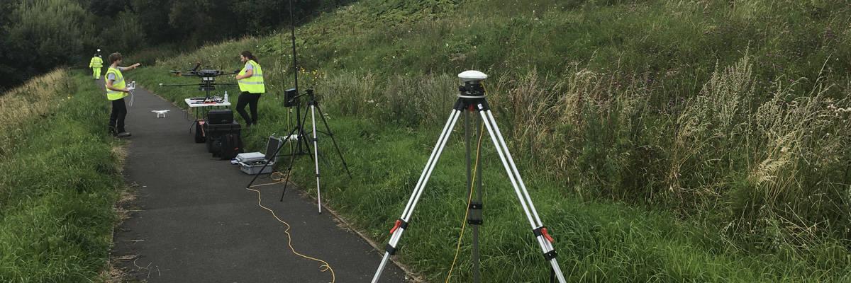 Surveyors and tripod on path
