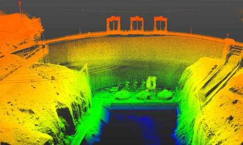 Bright orange, yellow and green point cloud showing the detail of a dam structure in USA including powerlines, water outlets.