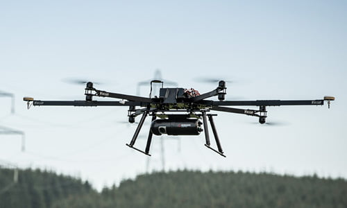 Multicopter drone with Routescene LidarPod underneath flying above forestry with powerline behind.