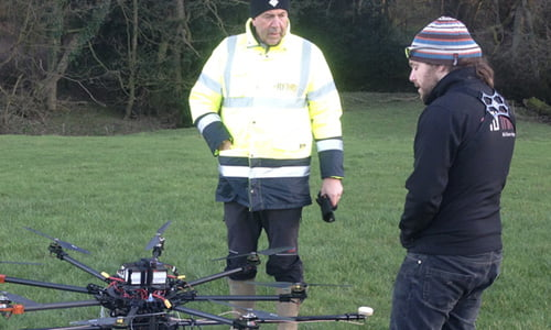 Three male surveyors in yellow hi-vis vests setting up Routescene UAV LiDAR system on a drone.